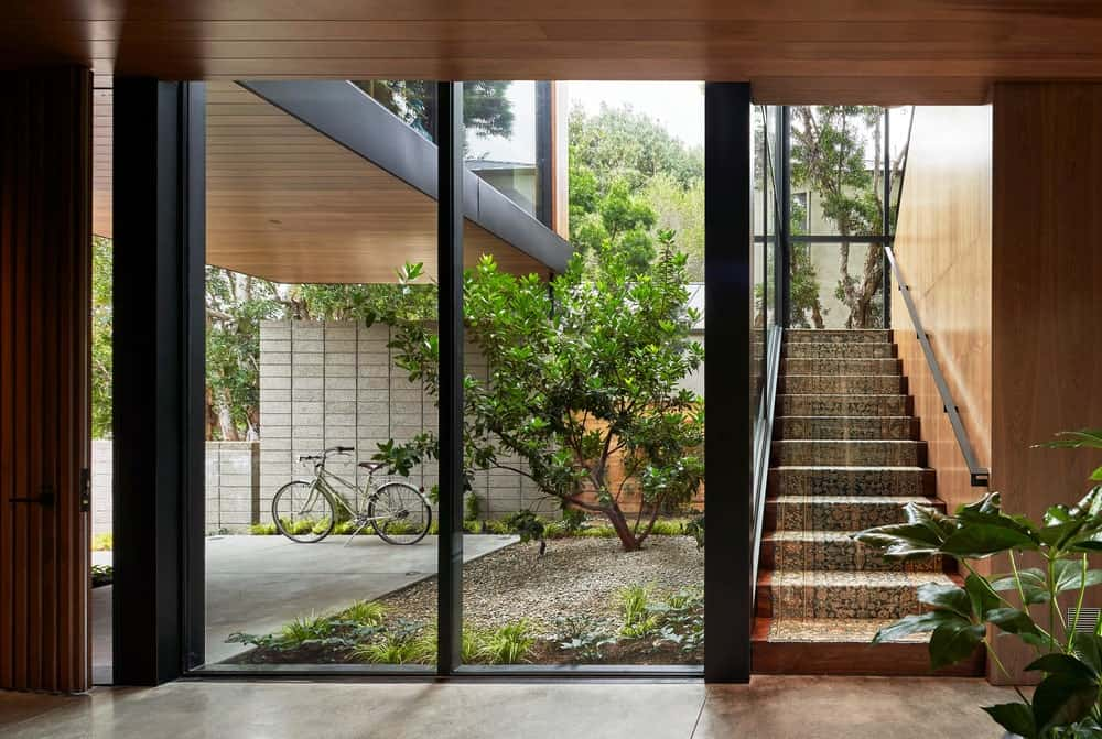 This is the foyer of the house bathed in natural lights from the glass wall beside the staircase and the wooden main door.