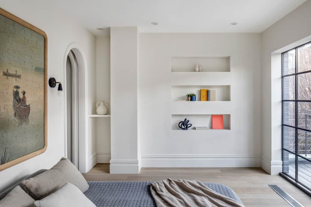 This is the simple bedroom with a cottage bed topped with a large painting and an opposite bright wall with built-in shelves brightened by the French-style glass door.