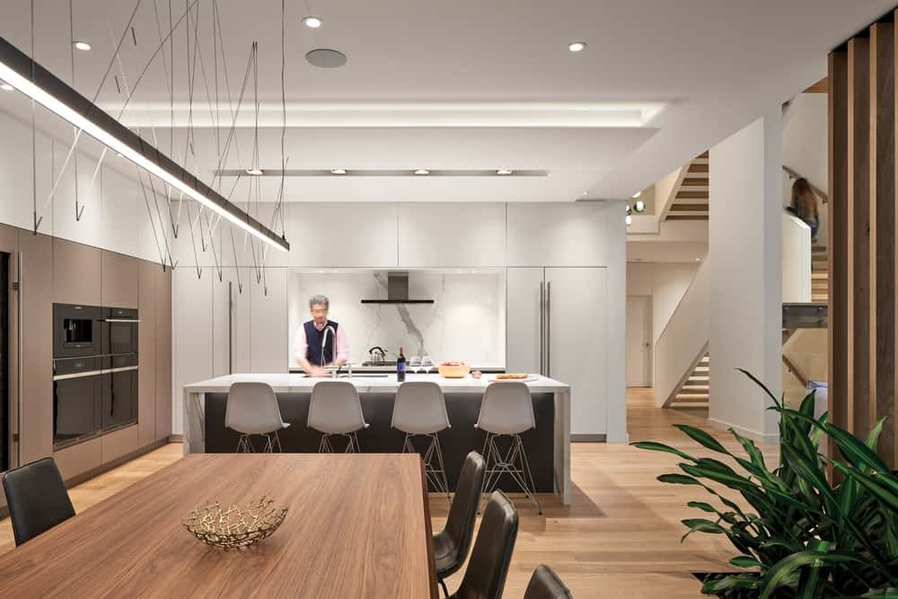 This is a view of the kitchen from the vantage of the dining area topped with a long and thin lighting hanging from the white ceiling over the wooden dining table.