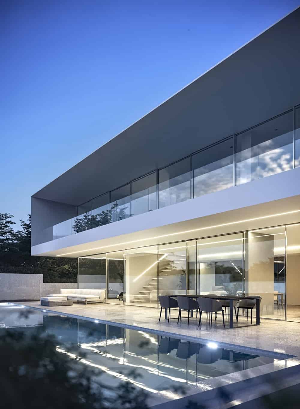 This is a close look at the back of the house feasturing an unlit second level balcony making the glass railings stand out. This view also shows the interiors of the house.