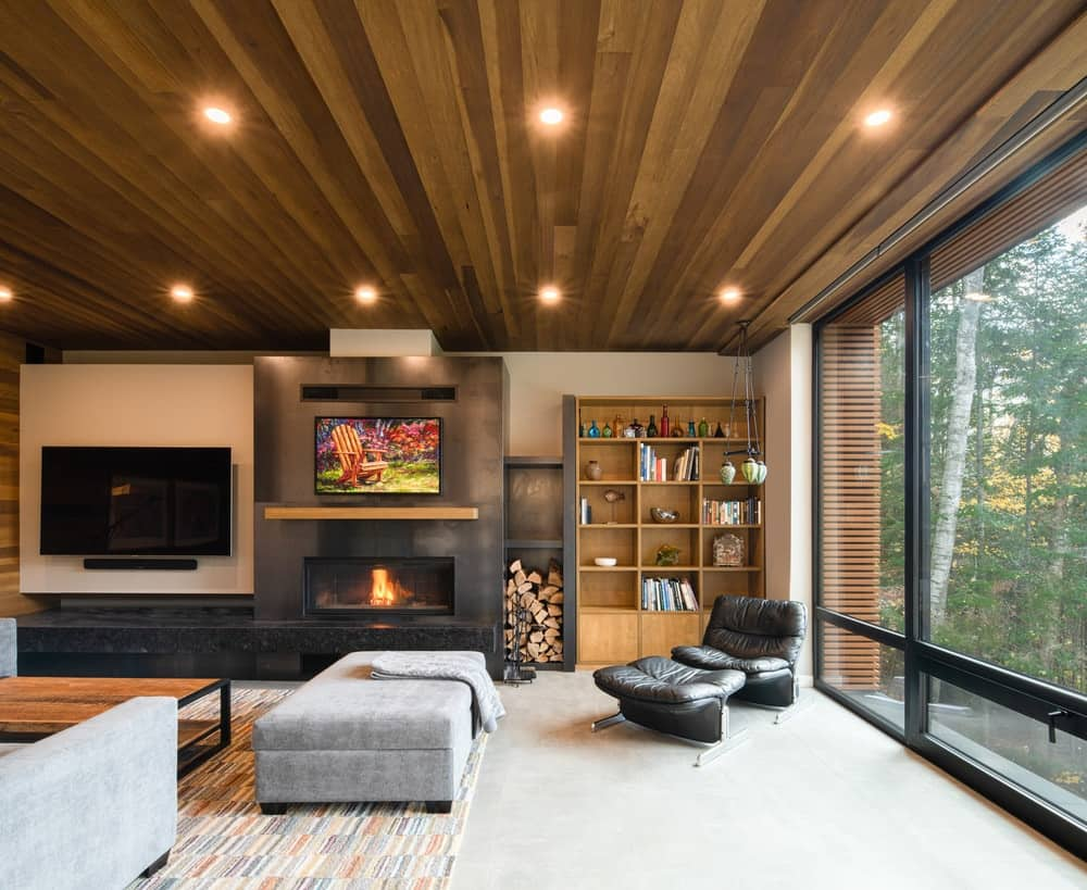 This is a view of the living room with a wooden shiplap ceiling and dark built-in structure with a fireplace and a wall-mounted TV.