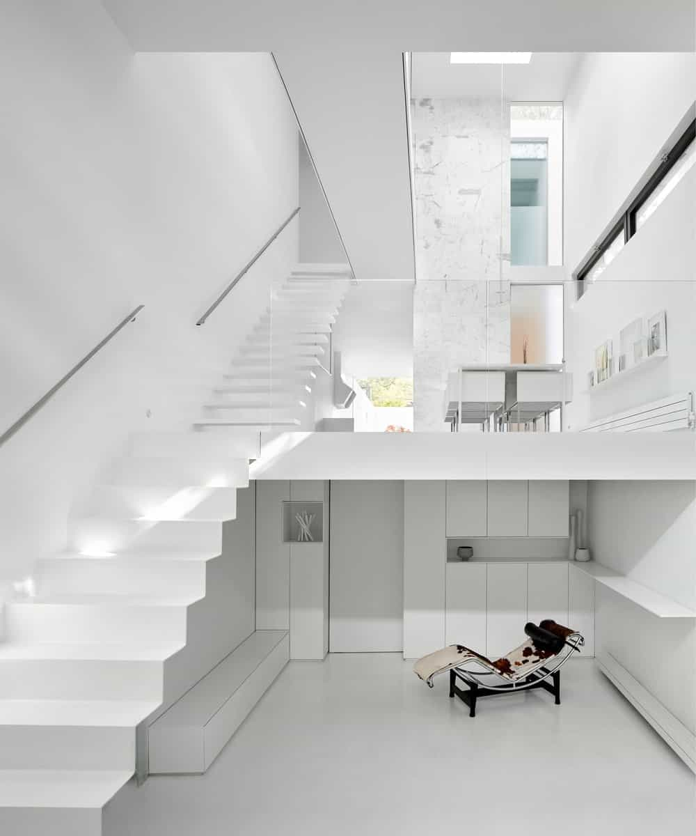 This view of the house interior shows the dining area on the ground level and a lounge chair at the basement level that stands outa against the white elements.