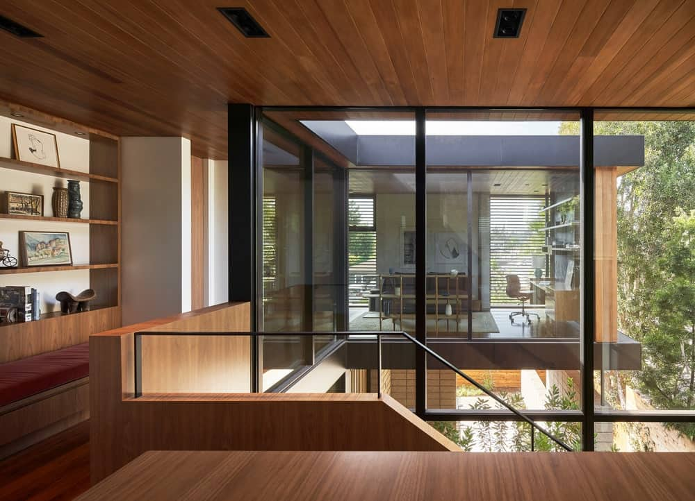 The glass walls of the staircase reaches to the second-level landing with wooden tones on its ceiling, walls and flooring.