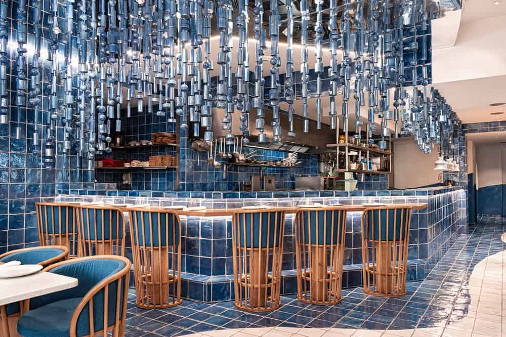 This is a close look at the large bar that is paired with wooden stools that has blue cushions to pair with the theme.
