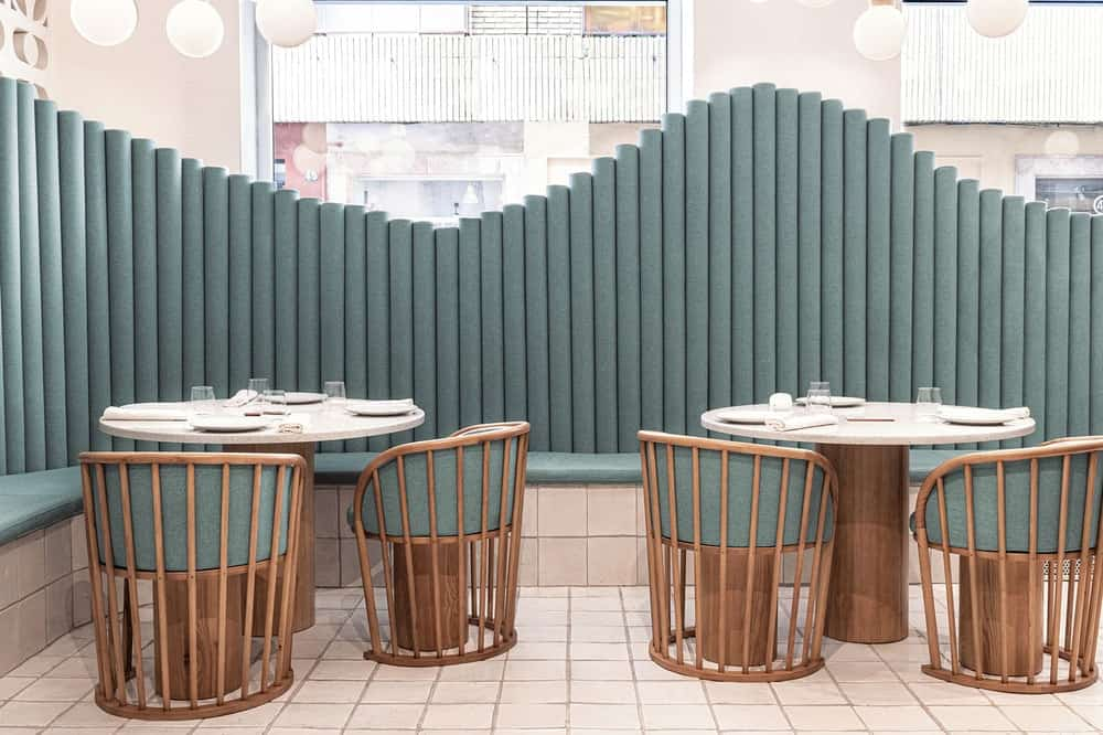 The wooden chairs of the booths has cushions on it that matches with the tone of the built-in benches.