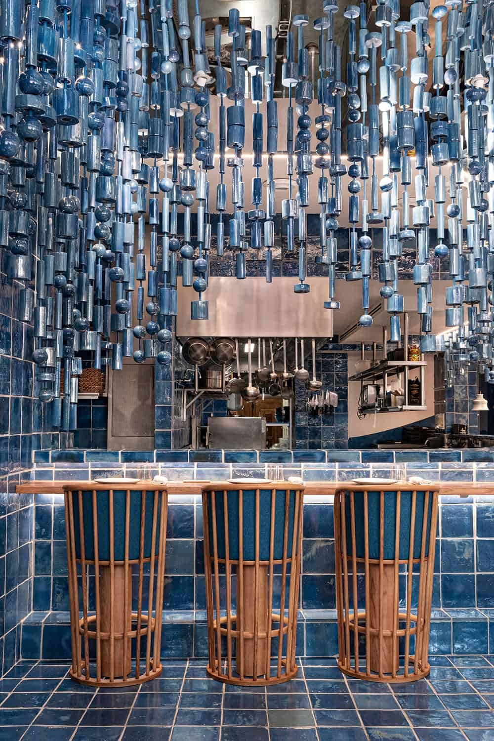 This is a close look at the bar that has stools, tiles and hanging decorations that matches in tone.