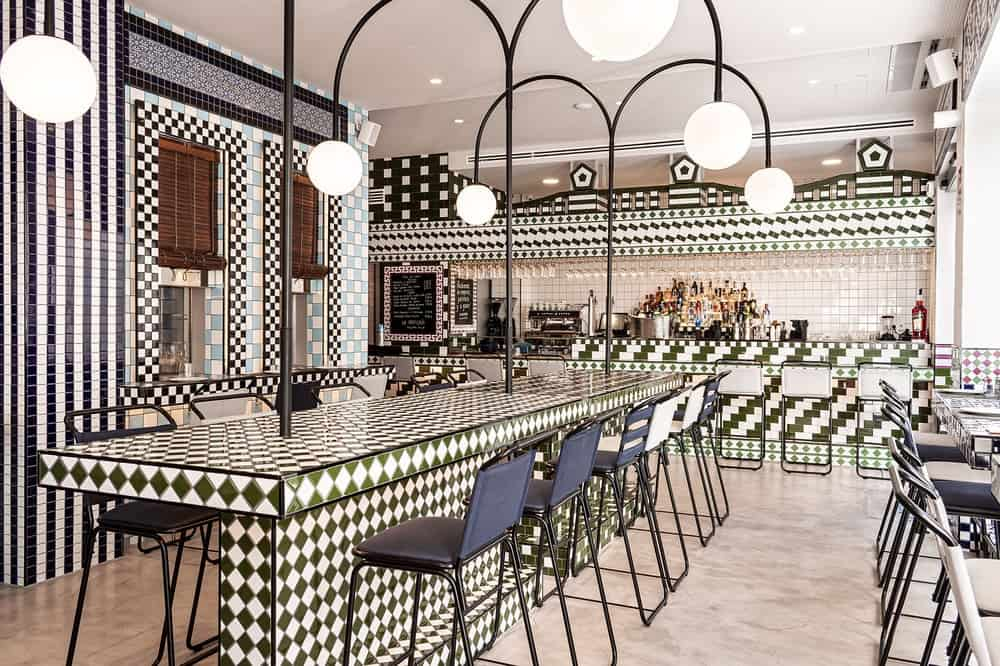 This is a close look at the bar area with stools, decorative lighting and green checkered tiles.
