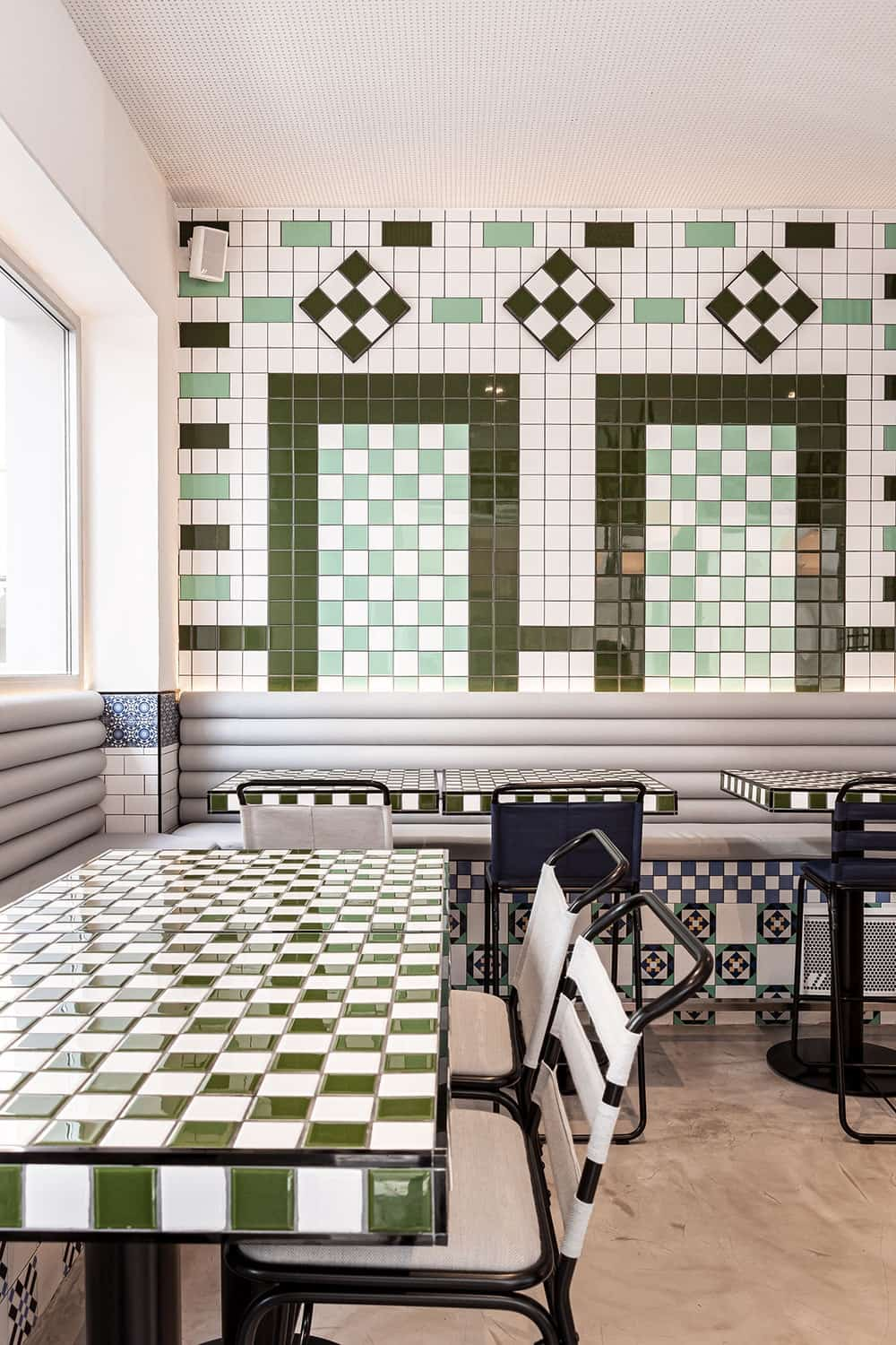 This is a close look at the booth sections of the restaurant with cushioned built-in benches paired with checkered tables.