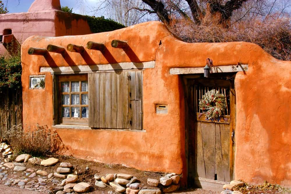 A close look at a small and old adobe-style home with an earthy tone to its exterior.