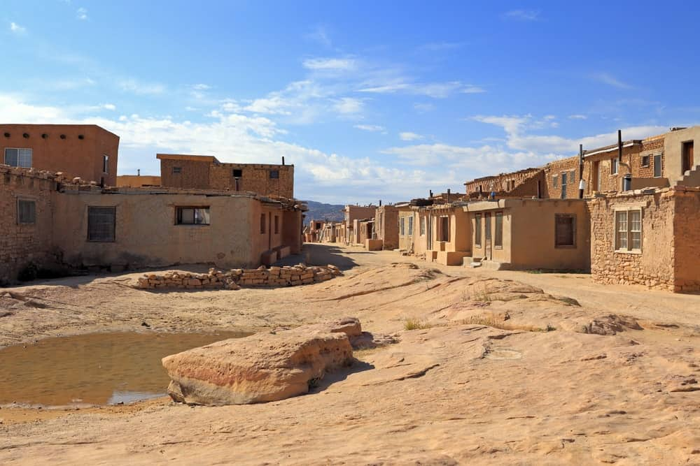 A close look at a collection of adobe houses with the same earthy tone as the soil surrounding them.