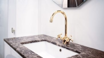 A bathroom sink with black marble countertop and golden bridge faucet.