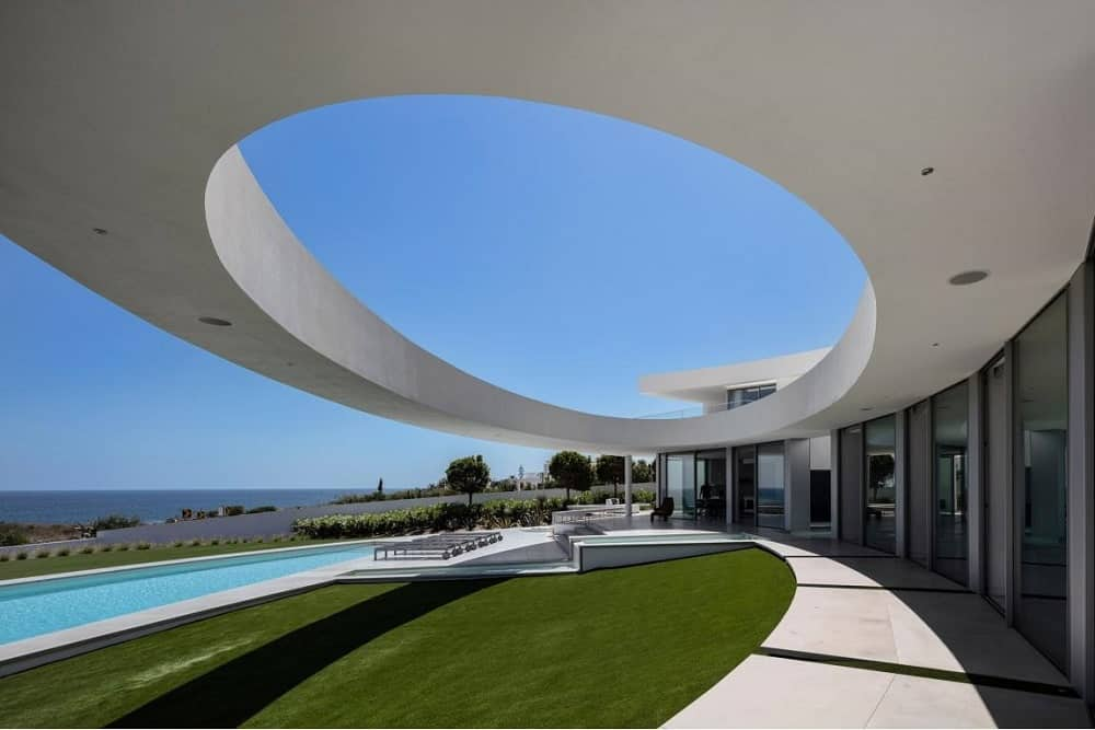 This is a view of the concrete structure over the backyard lawn leading to the pool with a large elliptical design.