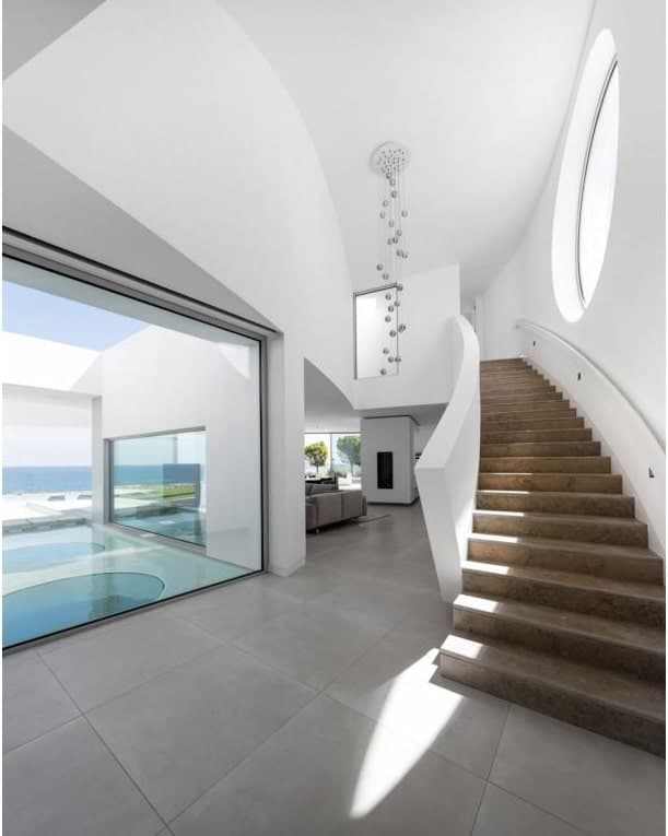 Upon entry of the house, you are welcomed by this bright foyer with a staircase on one side and a view of the landscape pond on the other side through a glass wall.