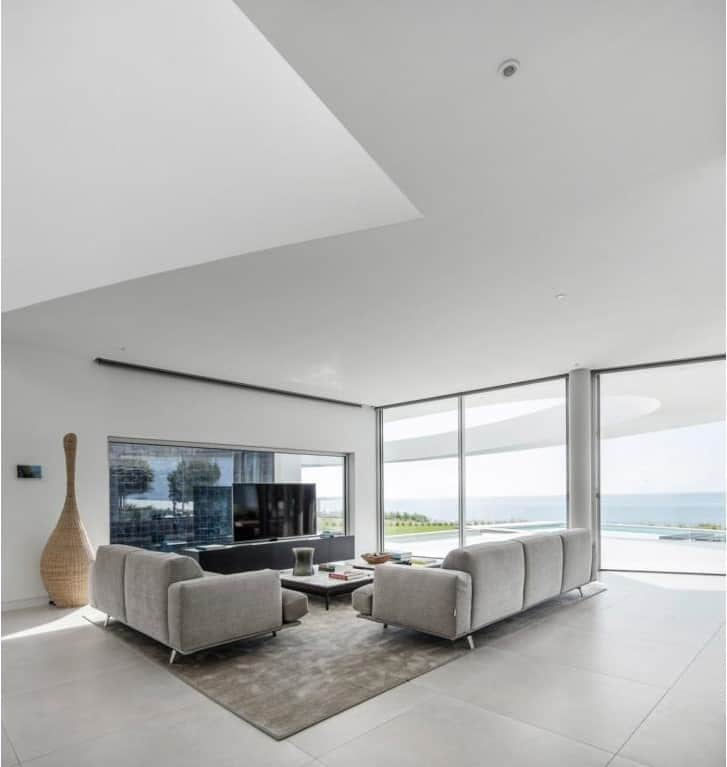 This is the bright and airy living room with gray sectional sofas facing the TV against the glass wall of the pond.