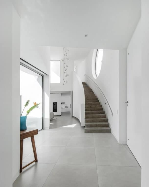 This is a view of the foyer from the main door showcasing the white walls, natural lighting, staircase and wooden console table topped with a vase.