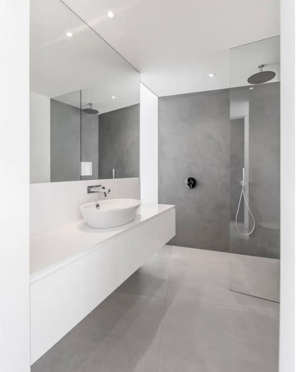The bathroom has a bright floating vanity and a freestanding sink. On the far side is the gray wall of the shower area.