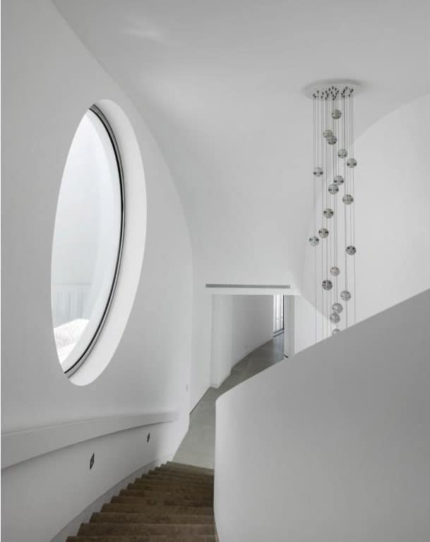 This is a look at the staircase from the vantage of the second-level landing showcasing the large round window and a decorative chandelier over the foyer.