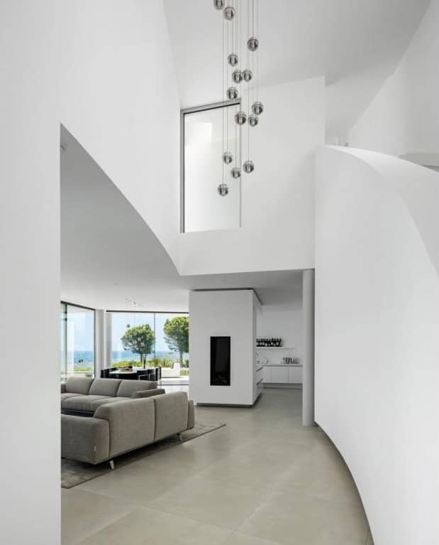 The tall ceiling and tall white wall of the foyer on the side of the staircase is adorned with a decorative chandelier and a glass window above.