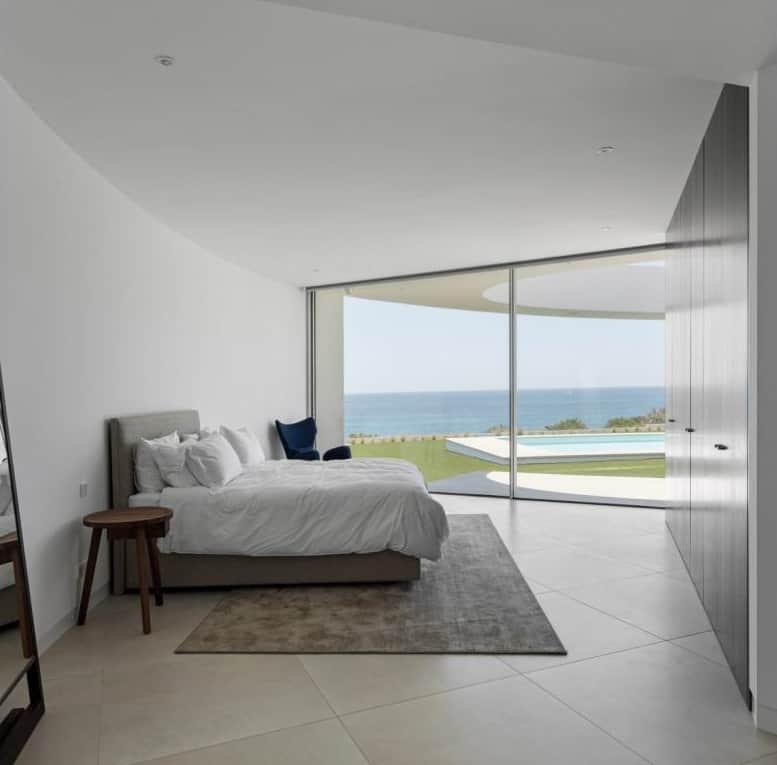 This is a simple bedroom with a large bed that has cushioned headboard bathed in natural lighting from the large glass wall on the far side with a view of the backyard.