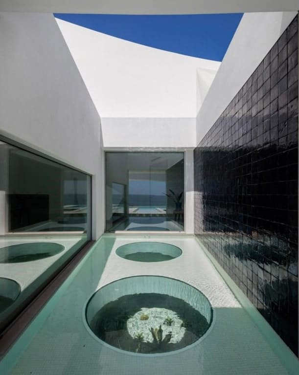 This is a look at the landscape pond from the vantage of the walkway showcasing the glass walls and black textured wall.