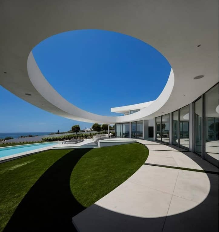 Here is another look at the unique elliptical design over the backyard poolside area bordered with glass walls on side facing the pool.