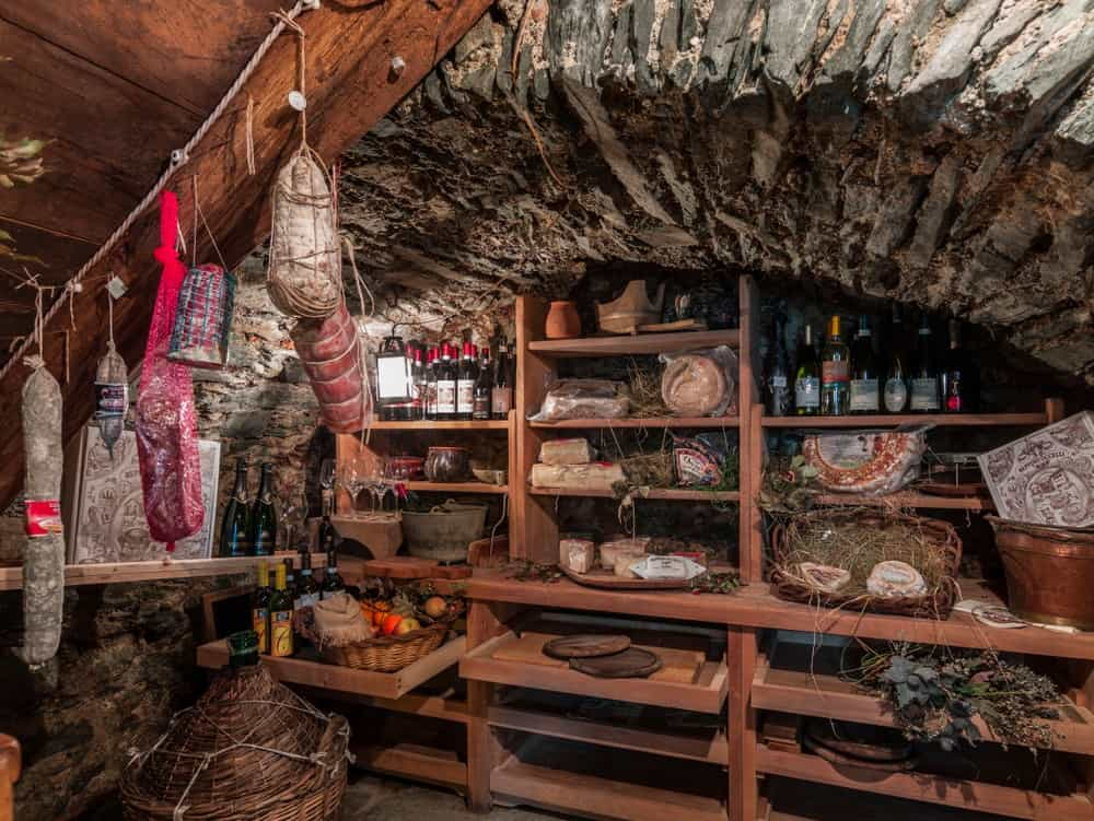 A root cellar pantry with preserved cheese, meat and wine.