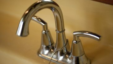 This is a close look at a double handle faucet in the bathroom sink.