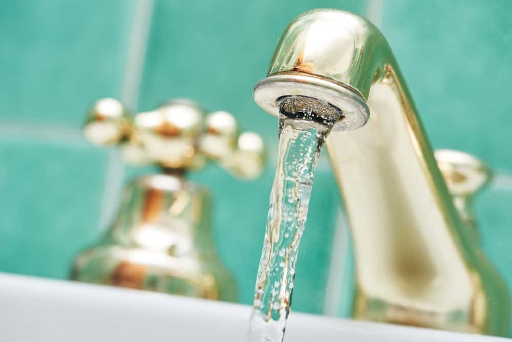 This is a close look at a bathroom double handle faucet against a green tiled backsplash.