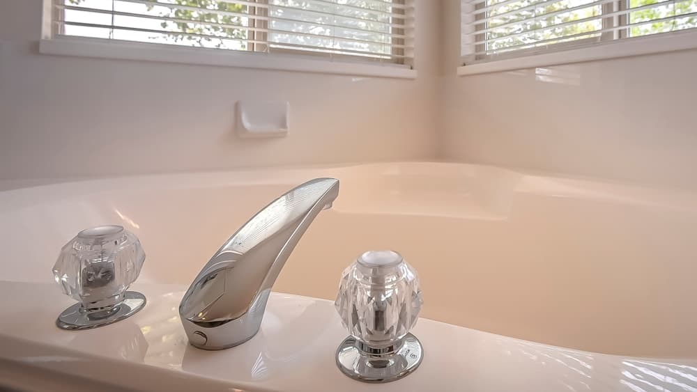 A double handle faucet attached to the bathtub in the bathroom.