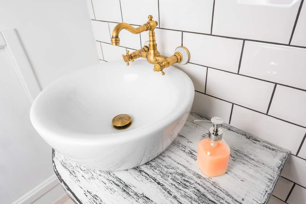 A bathroom vanity with a freestanding sink paired with a golden double handle faucet.
