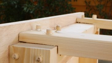A close look at furniture being assembled with wooden dowel joints.