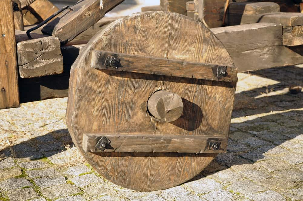 A close look at an old cart with wooden wheels.