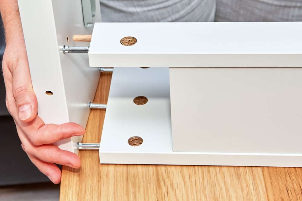 A close look at a man assembling furniture with steel dowel joints.