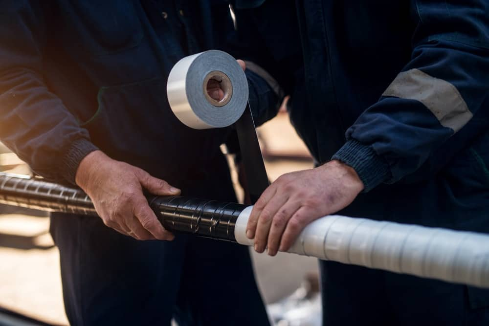 A close look at workers coating a pipe with duct tape.