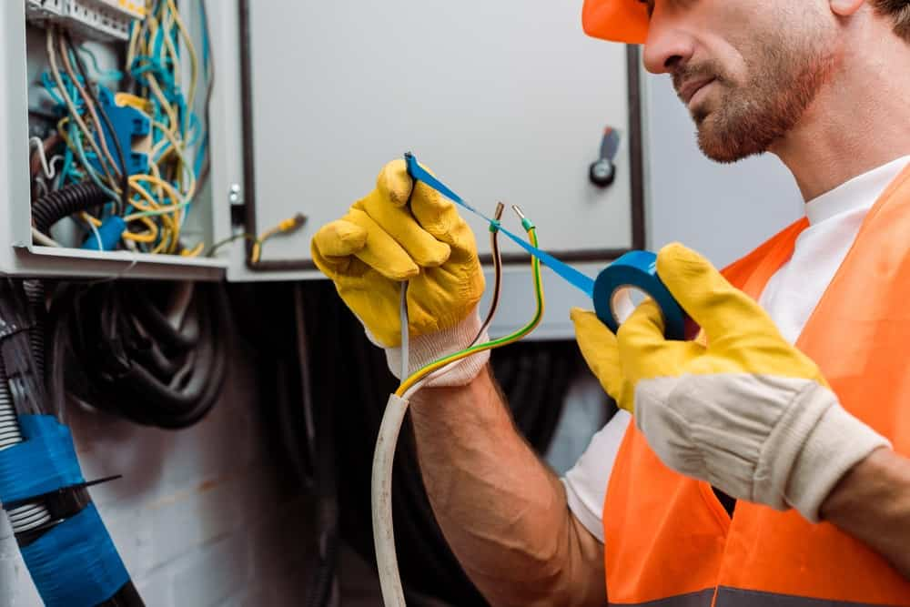 An electrician coating the wiring with electrical tape.