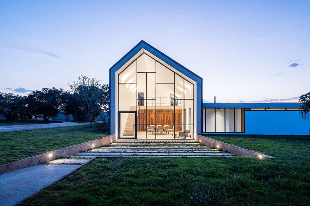 This is a front view of the house with a large glass wall showcasing the large interiors with glowing warm lighting and bright walls.
