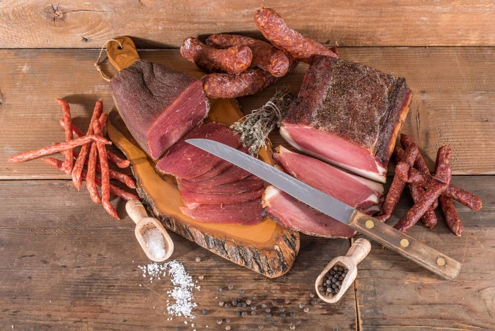 Various cured meat on a chopping board.