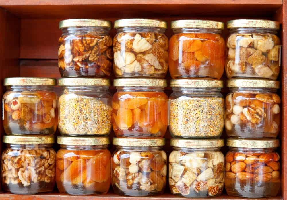 Various jars of fermenting food in a shelf.