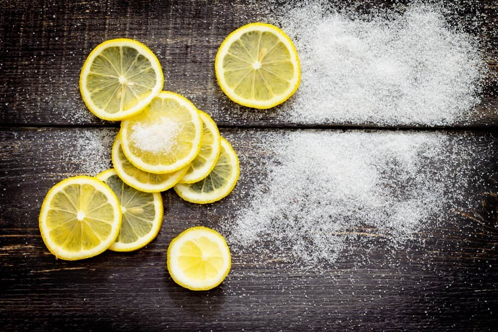 Slices of lemon and sugar on a wooden table.