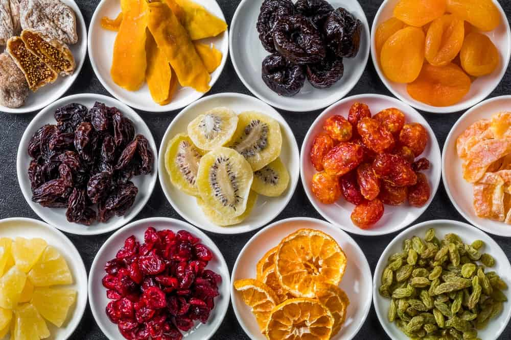 Various dried fruits on white plates.