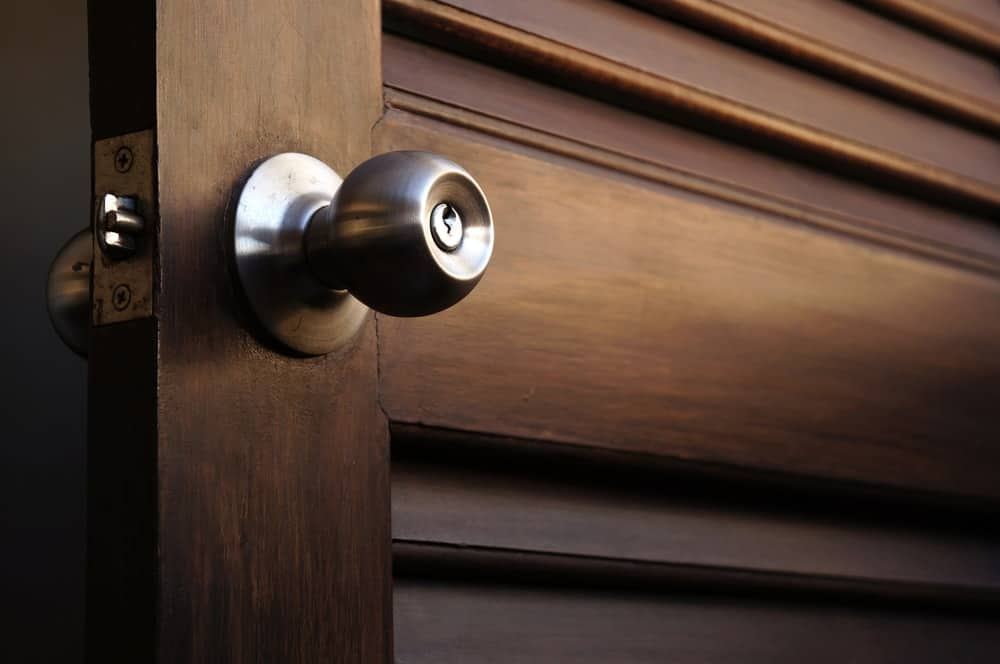 A close look at a wooden door with a stainless steel set of doorknob.