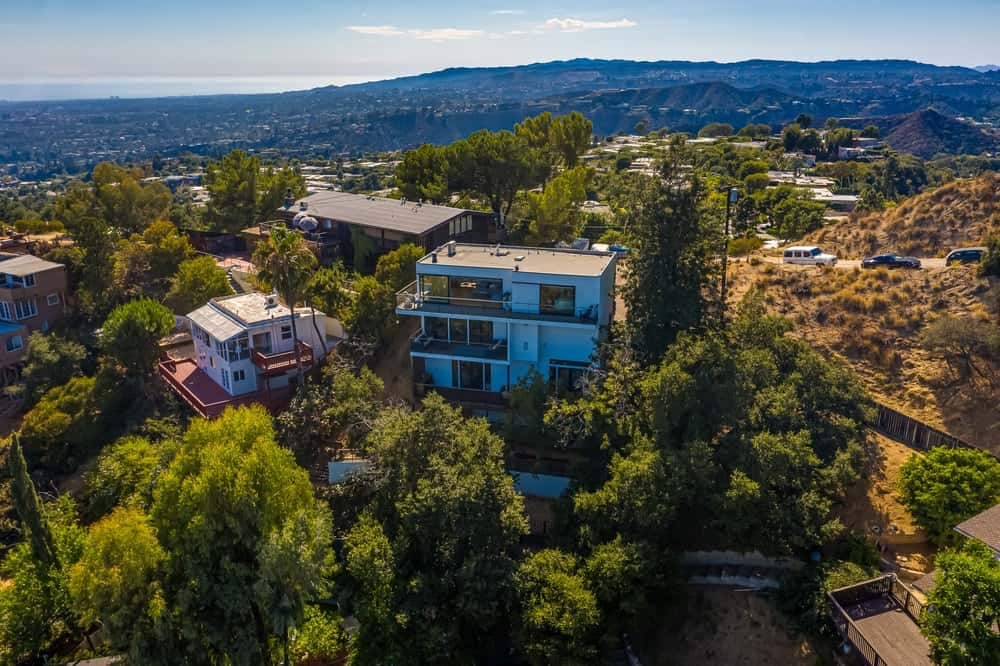 This is an aerial view of the house showcasing the multiple decks of the house, its bright exterior walls and the surrounding landscape of tall trees. Image courtesy of Toptenrealestatedeals.com.