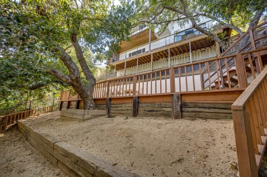 This is a look at the back of the house facing the cliff. You can see here the wooden elements of the house that complement the white walls along with tall trees and multiple levels of balcony. Image courtesy of Toptenrealestatedeals.com.