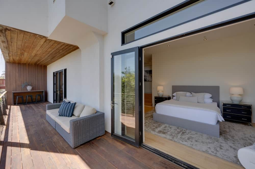 A few steps from the bedroom is the wooden deck balcony with comfortable furniture and bright white walls. Image courtesy of Toptenrealestatedeals.com.