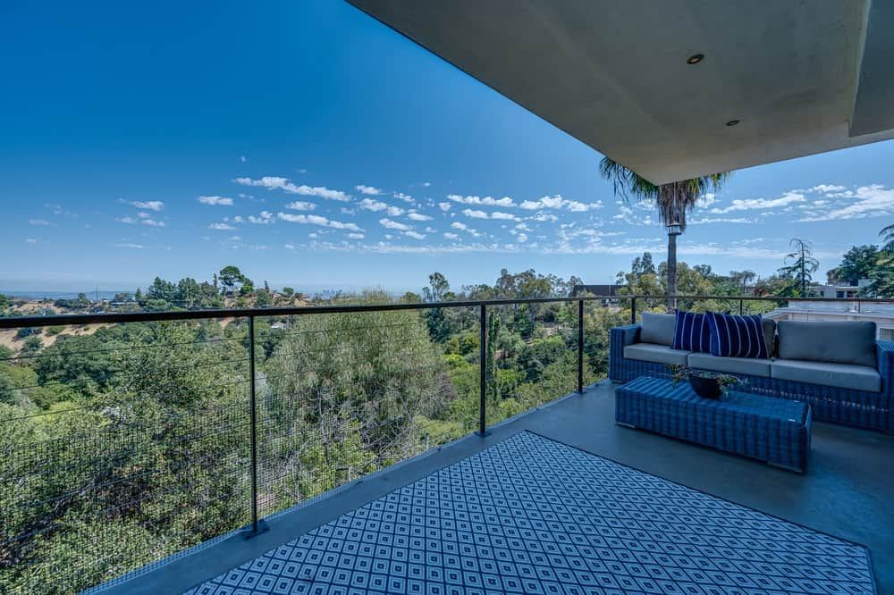 This is the top balcony fitted with a comfortable outdoor sofa and a coffee table. These are complemented by the sweeping views of the surrounding landscape. Image courtesy of Toptenrealestatedeals.com.
