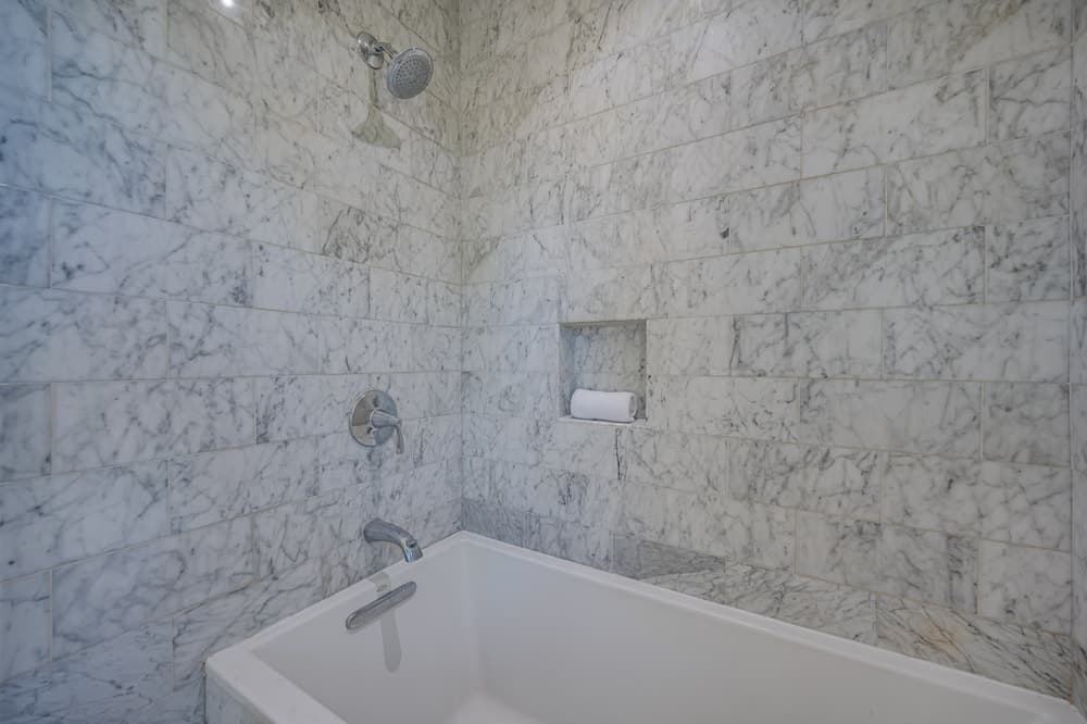 This is the corner of the bathroom showcasing the white bathtub that is complemented by the surrounding white marble tiles on the walls. Image courtesy of Toptenrealestatedeals.com.