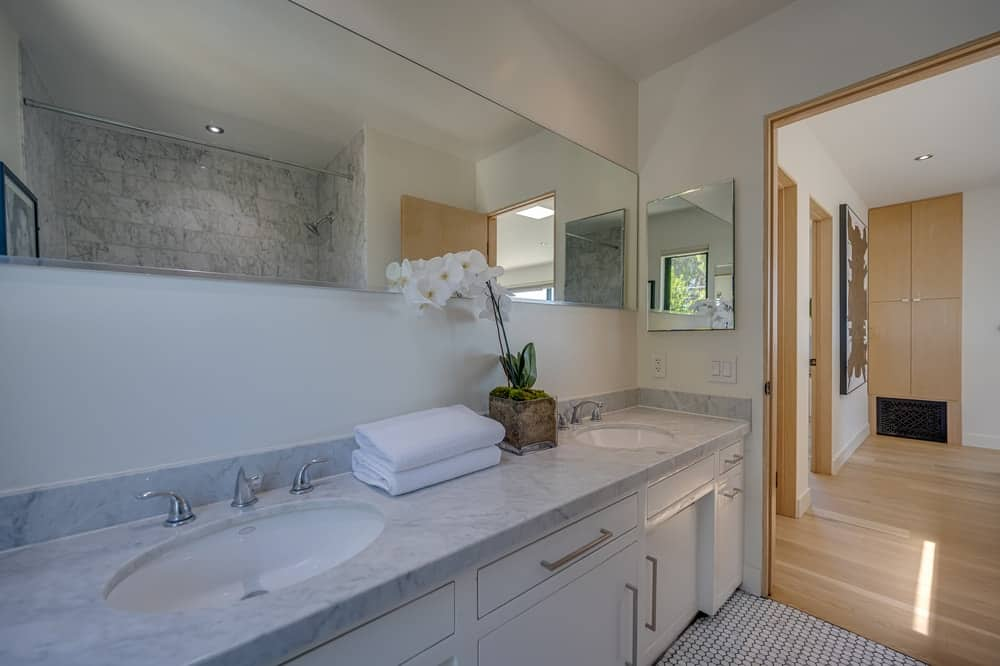 This is a close look at the vanity area of the bathroom with a large two-sink vanity topped with a large mirror. Image courtesy of Toptenrealestatedeals.com.