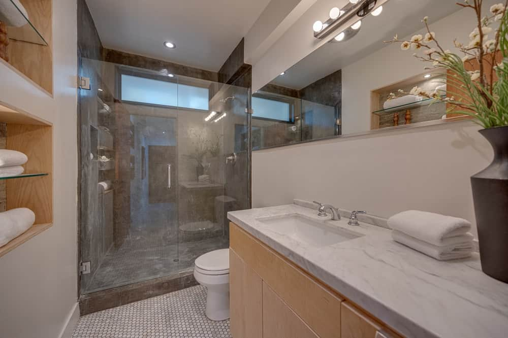 This other bedroom has a glass-enclosed shower area on the far side by the white porcelain toilet. Image courtesy of Toptenrealestatedeals.com.