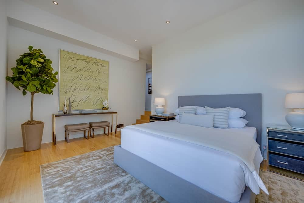 This bedroom has a small study area on the side of the bed adorned with a potted plant. Image courtesy of Toptenrealestatedeals.com.
