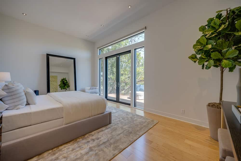 This other view of the bedroom showcases the gray bed frame that matches the area rug on the hardwood flooring. These are then complemented by the bright glass doors. Image courtesy of Toptenrealestatedeals.com.